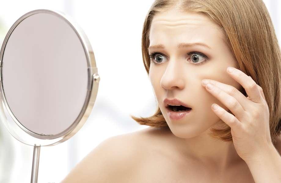 mujer acné espejo
